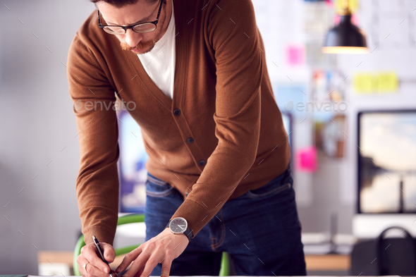 Male Architect Standing At Desk In Office Amending Building Plans - Stock Photo - Images