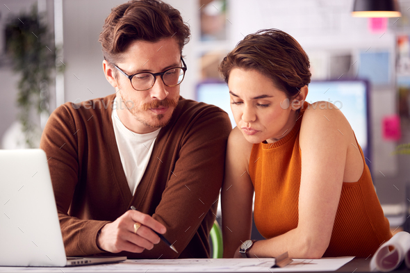 Male And Female Architects In Office Working At Desk On Laptop And Looking At Plans - Stock Photo - Images