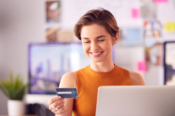 Female Architect In Office Working At Desk Making Online Purchase Using Credit Card On Laptop - Stock Photo - Images