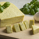 Piece of Dutch organic cheese with garlic and basil leaves - PhotoDune Item for Sale