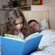 Happy cute girl lying in bed with her father who is reading a book - PhotoDune Item for Sale