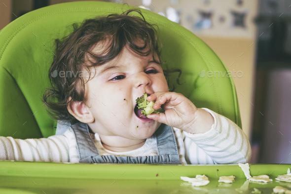 Baby eating food in her green highchair - Stock Photo - Images