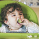 Baby eating food in her green highchair - PhotoDune Item for Sale