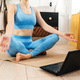 Young woman practicing yoga indoor, watch tutorial. - PhotoDune Item for Sale