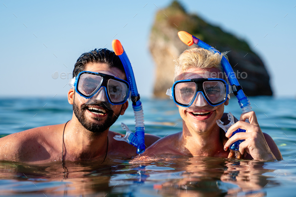 Group of happy fit friends go scuba diving together on summer vacation - Stock Photo - Images