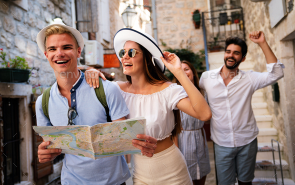 Happy group of friends tourists sightseeing in city on vacation - Stock Photo - Images