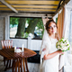 Charming bride at wedding bouquet at her hands near window at cafe - PhotoDune Item for Sale