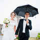 Wedding couple walking under rain with umbrella background tower of old castle - PhotoDune Item for Sale