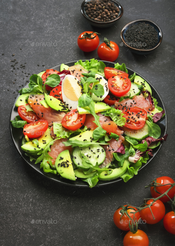 Fresh salad with salted salmon, avocado, egg, sesame seeds, olive oil, tomatoes and mixed herbs - Stock Photo - Images