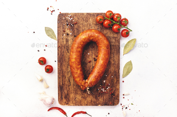 Smoked sausage circle on white kitchen table with spices, tomatoes and garlic - Stock Photo - Images