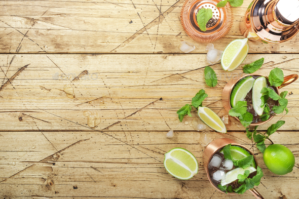 Moscow mule cocktail in copper mug with lime, ginger beer, vodka and mint. Wooden bar counter - Stock Photo - Images