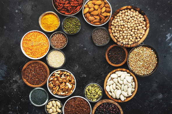 Selection of superfoods, legumes, cereals, nuts, seeds in bowls on black background - Stock Photo - Images