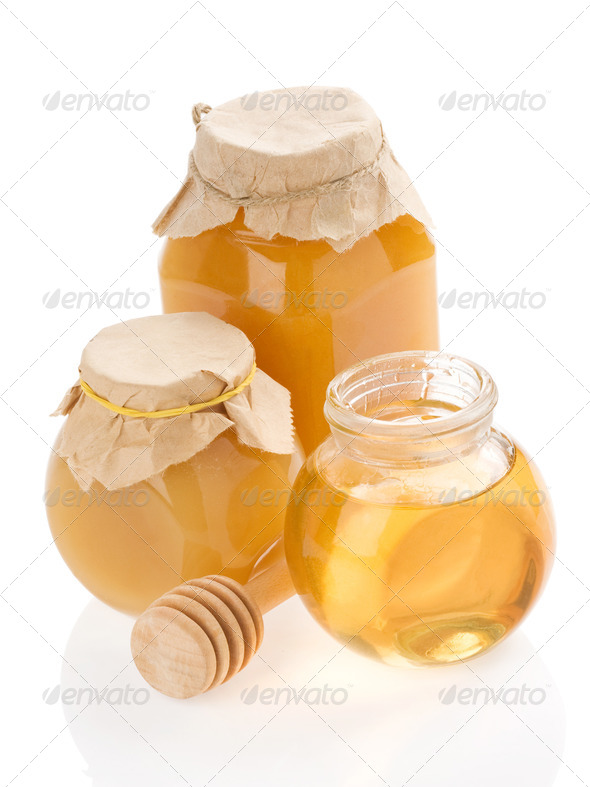 glass jar full of honey and stick on white - Stock Photo - Images