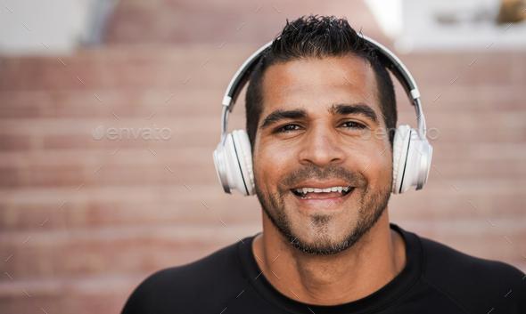 Hispanic man listening music with headphones - Focus on face - Stock Photo - Images
