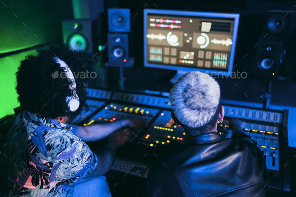 Musician and sound engineer mixing new album inside boutique recording studio - Stock Photo - Images