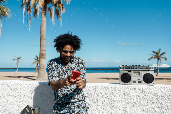 African man listening music with vintage boombox stereo outdoor while using mobile phone - Stock Photo - Images