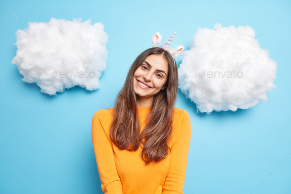 Lovely charming woman with long dark hair tilts head smiles gently wears unicorn headband long sleev - Stock Photo - Images