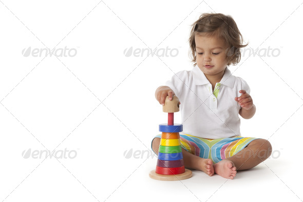 Toddler girl playing with colored bricks - Stock Photo - Images