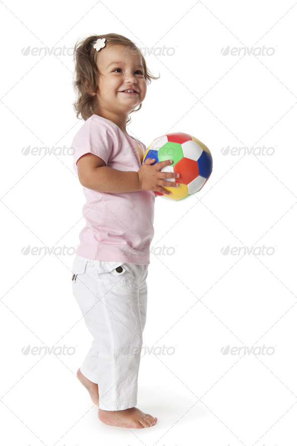 Toddler girl playing with a colored ball - Stock Photo - Images