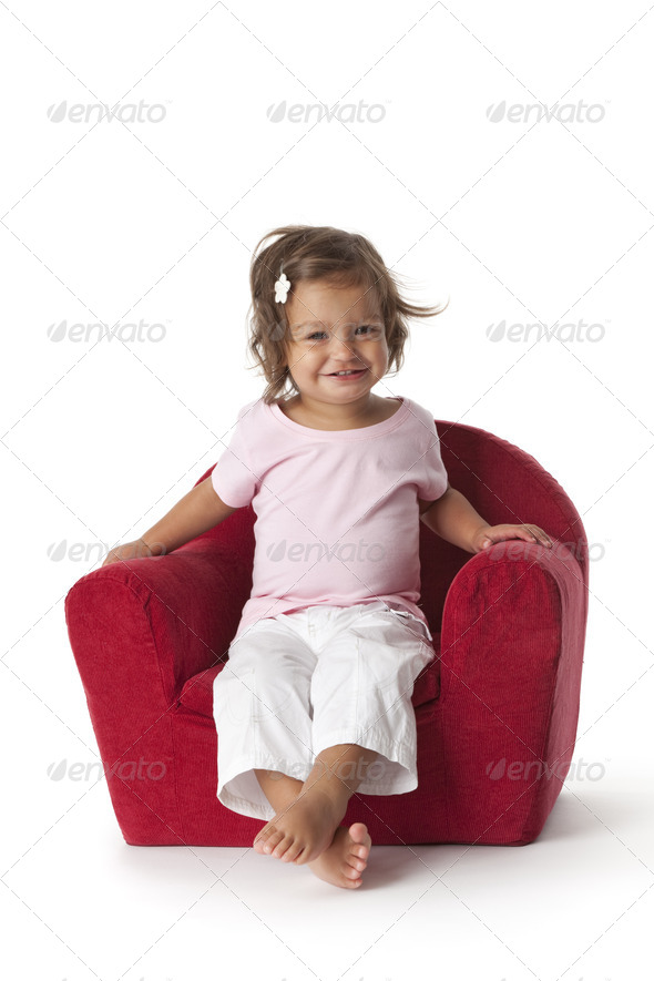 Toddler girl making fun in an armchair - Stock Photo - Images