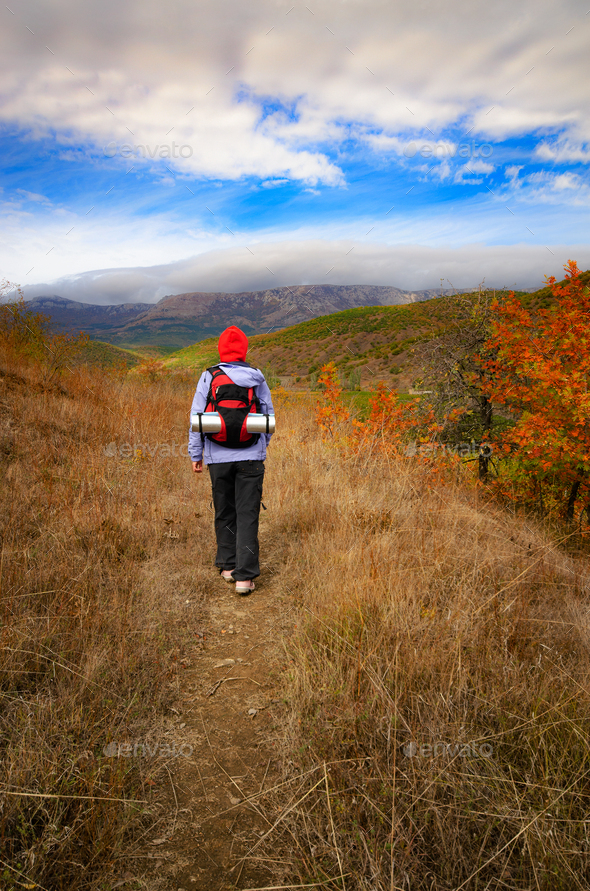 Middle aged active caucasian female model with backpack walk in mountains autumn time - Stock Photo - Images