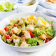 Caesar salad with lettuce, chicken, avocado, cherry tomatoes and croutons on light table. - PhotoDune Item for Sale
