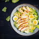 Caesar salad with lettuce, chicken, avocado and croutons on dark table.  Top view, above, flat lay - PhotoDune Item for Sale