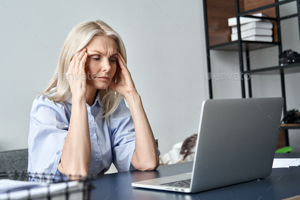 Stressed old business woman suffering from headache after computer work. - Stock Photo - Images