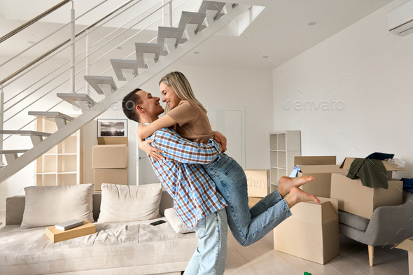 Happy young couple first time home owners hugging in living room on moving day. - Stock Photo - Images