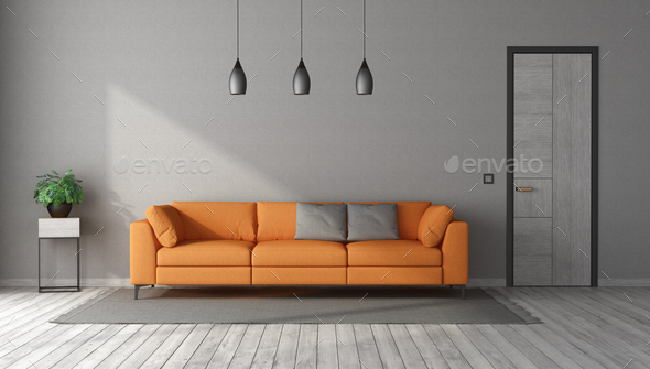 Orange sofa in a gray room with closed door - Stock Photo - Images