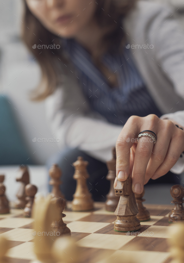 Woman playing chess and moving a piece - Stock Photo - Images
