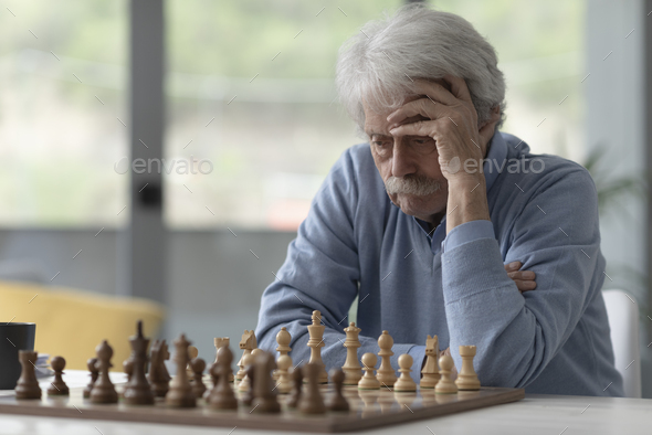 Focused senior man playing chess - Stock Photo - Images