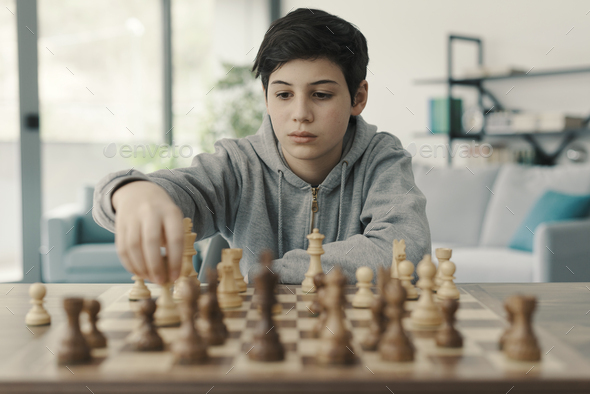 Boy playing chess at home - Stock Photo - Images