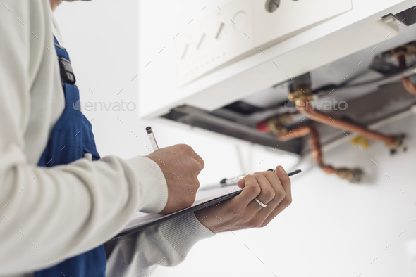 Professional plumber doing a boiler check - Stock Photo - Images