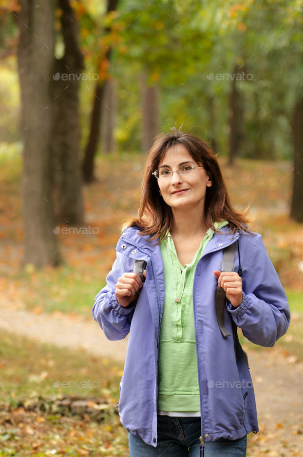 Middle aged active caucasian female model with backpack walk in woods autumn time - Stock Photo - Images