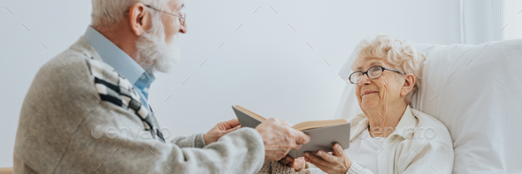 Grey elderly man hands a book to a senior friend lying on a hospital bed - Stock Photo - Images