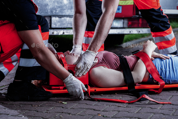 Professional medical rescuer bending over a car accident victim lying on a stretcher - Stock Photo - Images