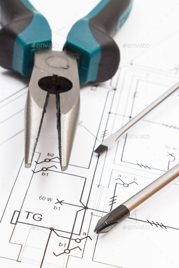 Metal pliers and screwdriver with electrical diagrams of house. Building home - Stock Photo - Images