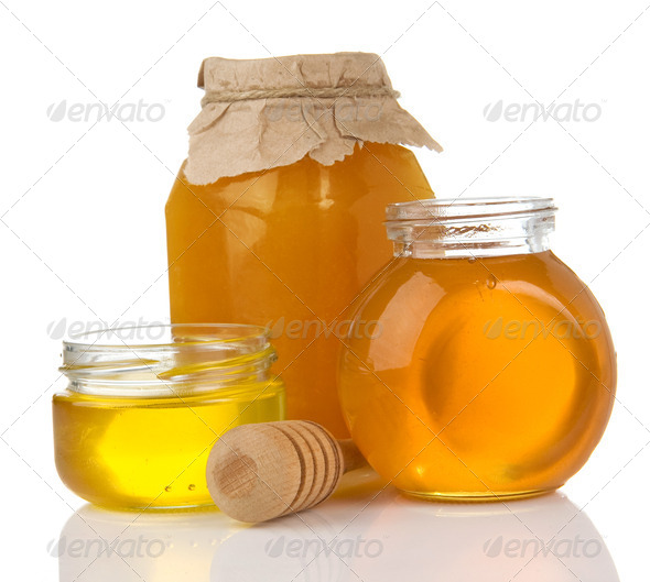 glass pot full of honey and stick - Stock Photo - Images