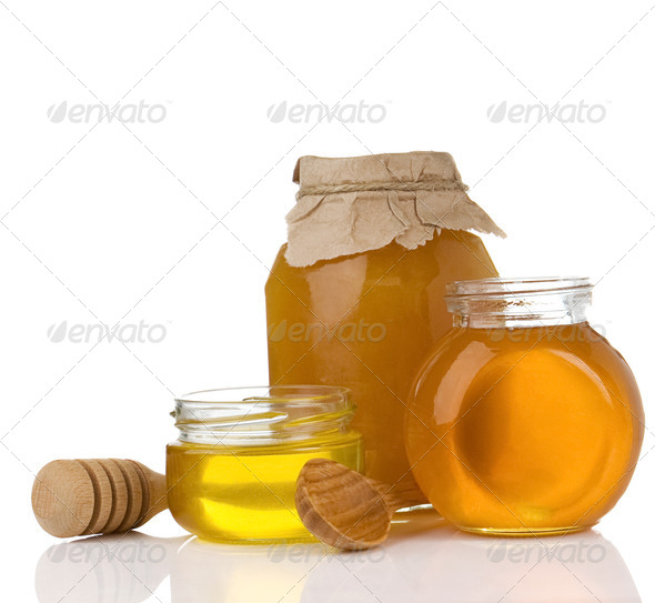 pot full of honey and stick isolated on white - Stock Photo - Images