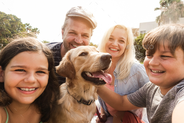 Young parents having fun with children and their pet outdoor at park in summer time - Stock Photo - Images