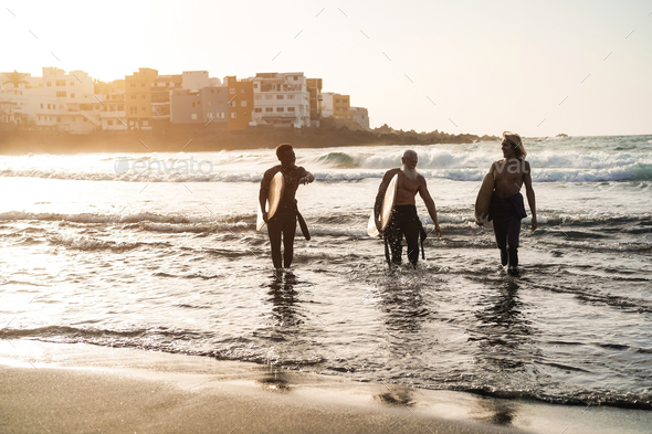 Multi generational surfer friends having fun after surf session on the beach - Main focus faces - Stock Photo - Images