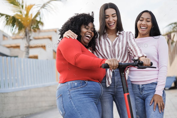 Happy latin girls having fun with electric scooter outdoor in city - Main focus on black woman face - Stock Photo - Images