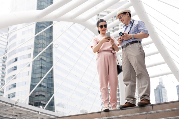 Senior Asian couple playing mobile outdoors. - Stock Photo - Images