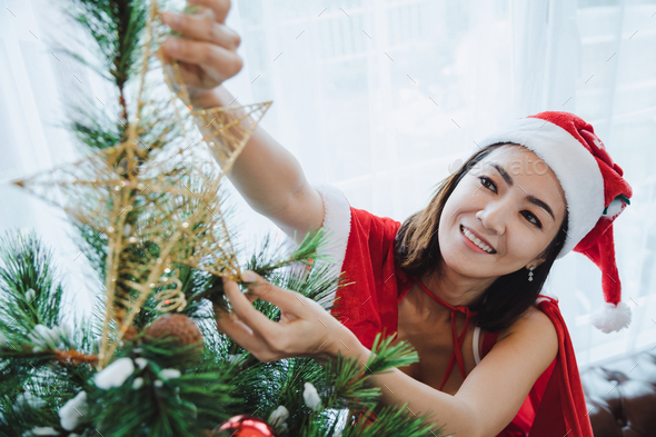 Sexy woman santa decorating Christmas trees. - Stock Photo - Images