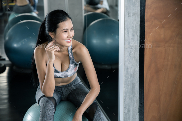Asian women in sport wear with smile sitting on yoga ball. - Stock Photo - Images