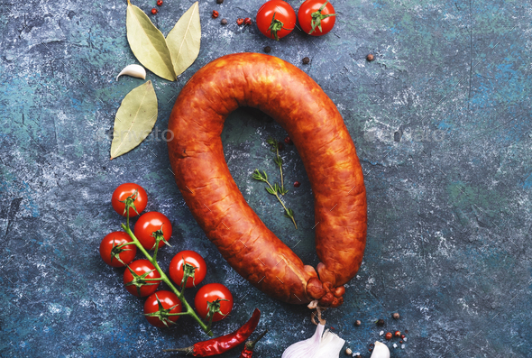 Smoked sausage circle on blue kitchen table with spices, tomatoes and garlic - Stock Photo - Images