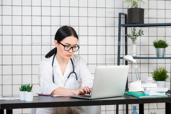 Young smiling woman sitting at desk, working on computer with medical documents in light office in - Stock Photo - Images