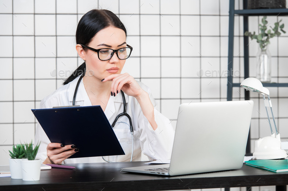 Female brunette doctor wears glasses using tablet, intelligent and lovely woman with the gadget and - Stock Photo - Images