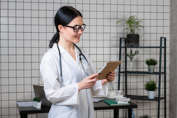 young female medical nurse using tablet computer in hospital office - Stock Photo - Images